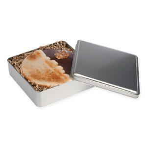 L-Schokotorte in Metallbox – die Schokotorte mit kleinen, feinen Schokoladenstücken wird mit einer leckeren Kakaoglasur umhüllt.