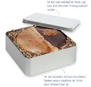 Abgeflämmte M-Schokotorte in Metallbox – diese feine Torte ist in Schoko- und Mandelmarzipan eingeschlagen und unter offenem Feuer abgeflämmt.