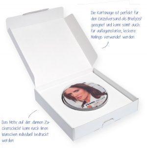M-Torte rund in Mailingbox – saftige runde Torte mit einem kräftigen Schokoladenüberzug, die Sie mit Ihrem Wunschmotiv direkt bedrucken können